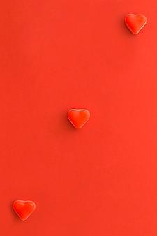 Vista aérea de caramelos de forma de corazón en superficie roja