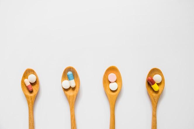 Vista aérea de cucharas de madera con pastillas aisladas sobre fondo blanco