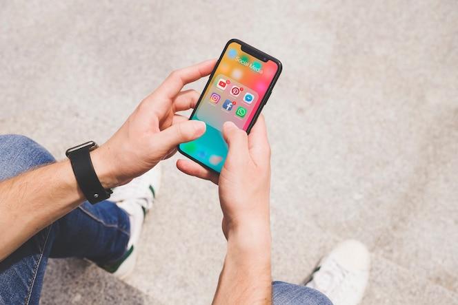 Vista aérea de la mano del hombre usando la aplicación de medios sociales en el móvil