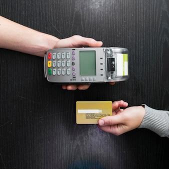 Vista aérea de manos sosteniendo el lector de tarjetas y la tarjeta de crédito en la mesa de madera