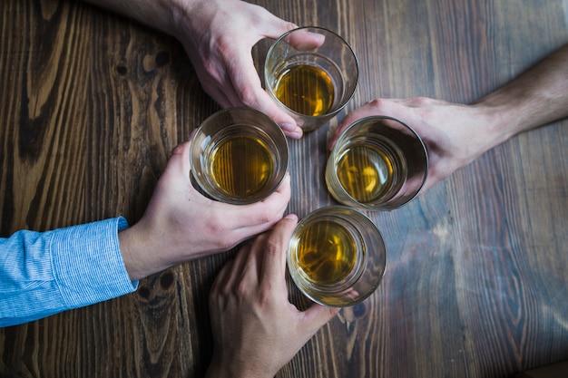 Vista aérea de manos sosteniendo vasos de bebidas en la mesa