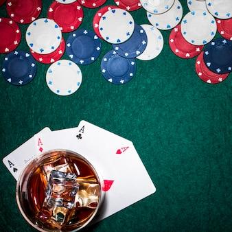 Vista aérea de vaso de whisky con cubitos de hielo sobre las tarjetas de ases en la mesa de póquer