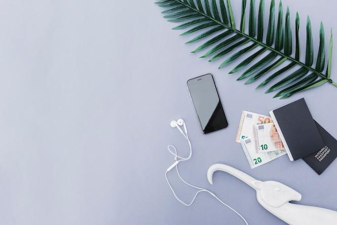 Vista aérea del teléfono móvil con auriculares, moneda euro, pasaporte y hojas sobre fondo gris