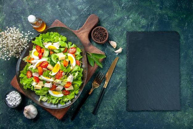 Vista aérea de la deliciosa ensalada con ingredientes frescos en la tabla de cortar de madera, especias, botella de aceite, cubiertos de ajos, sobre fondo negro de colores de mezcla