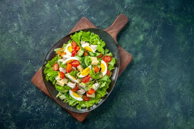 Vista aérea de una deliciosa ensalada con muchos ingredientes frescos en la tabla de cortar de madera sobre fondo de colores mezcla verde negro