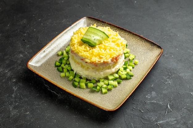Vista aérea de deliciosa ensalada servida con pepino picado sobre fondo oscuro