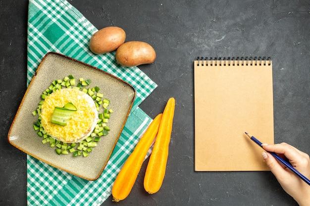 Vista aérea de la deliciosa ensalada servida con pepino picado en zanahorias y papas de toalla verde a la mitad dobladas junto al cuaderno sobre fondo oscuro