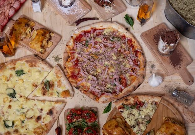 Vista aérea de deliciosas variedades de pizzas mediterráneas napolitanas recién preparadas y tapas en mesa de madera.