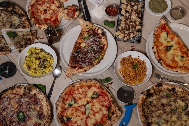 Vista aérea de deliciosas variedades de platos mediterráneos napolitanos recién preparados en mesa de madera