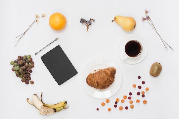 Una vista aérea del diario y la pluma con frutas; café y croissant aislado sobre fondo blanco
