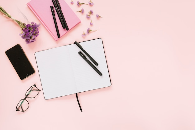 Vista aérea del diario; plumas; los anteojos; teléfono móvil y anteojos en fondo rosado