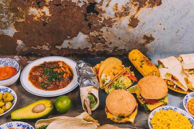 Vista aérea de diferentes platos mexicanos sobre fondo de metal viejo
