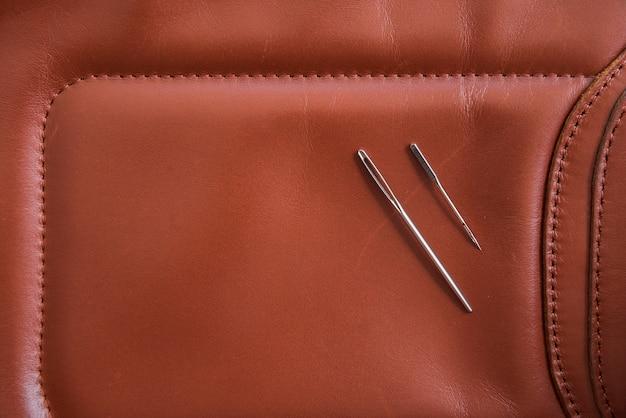Vista aérea de dos agujas en cuero marrón.