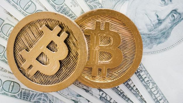 Una vista aérea de dos bitcoins sobre las notas de dólares estadounidenses extendidos