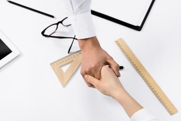 Vista aérea de dos empresarios que se dan la mano sobre el escritorio blanco.