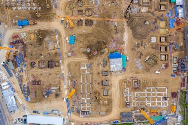Vista aérea del dron de la excavadora cargando el camión volquete en el sitio de construcción