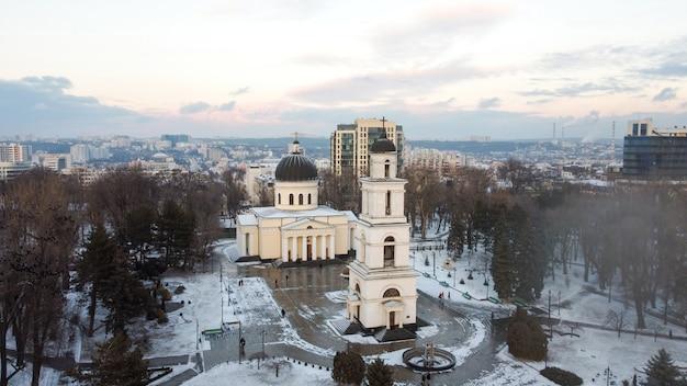 Vista aérea de drone del centro de chisinau en invierno. vista panorámica del parque central con nieve, árboles y varias personas que caminan, campanario, catedral, edificios en el fondo.