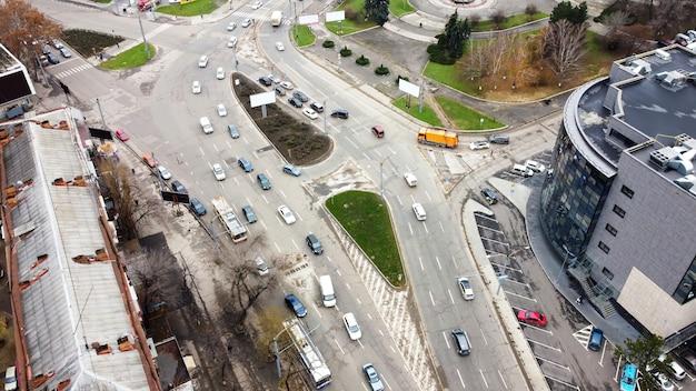 Vista aérea de drone de chisinau, carretera con varios coches en movimiento, intersección de rotonda, árboles desnudos, vista superior