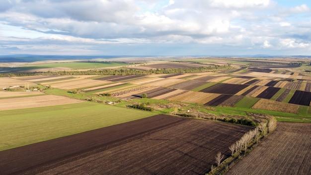 Vista aérea de drone de la naturaleza en moldavia, campos sembrados, filas de árboles, cielo nublado