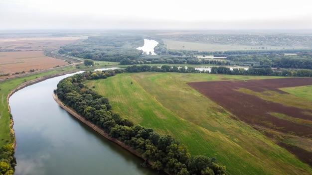 Vista aérea de drone de la naturaleza en moldavia, río flotante con cielo reflectante, campos verdes con árboles, niebla en el aire