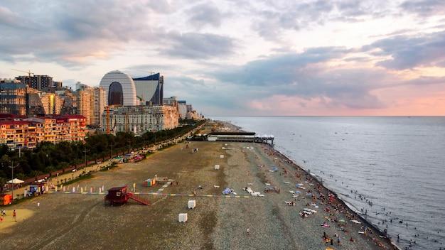 Vista aérea de drone de una playa al atardecer, hoteles y restaurantes del mar negro nadando