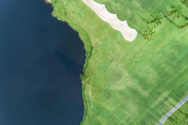 Vista aérea drone toma de arriba hacia abajo del hermoso campo de golf verde y palmeras vista de ángulo alto en verano