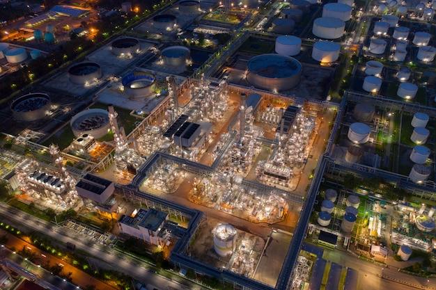Vista aérea de drones sobre una enorme fábrica de refinería de petróleo en la noche con muchos tanques de almacenamiento y torre de destilación.
