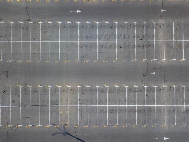 Vista aérea desde drones voladores hasta marcas de estacionamiento con lugares numerados. fondo de estacionamiento. vista superior