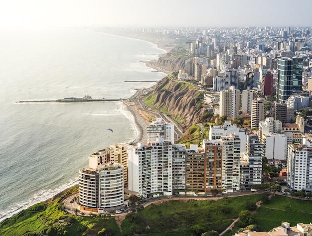 Vista aérea de los edificios, un acantilado y la orilla del mar en lima, perú.