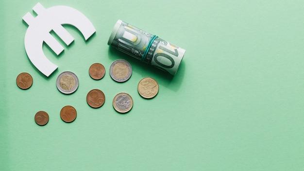 Vista aérea de enrollada nota de cien euros con símbolo y monedas en superficie verde