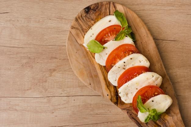 Una vista aérea de la ensalada caprese italiana con rodajas de queso mozzarella; albahaca y tomates en el tablero de servir