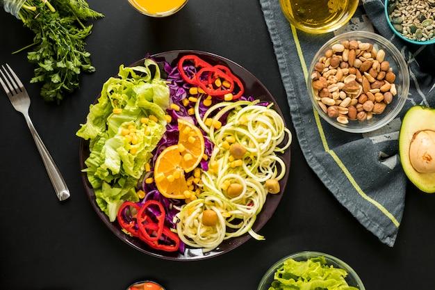 Vista aérea de ensalada saludable adornada en placa con derivas y tenedor sobre fondo negro
