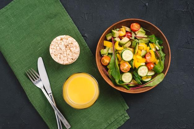 Una vista aérea de la ensalada de verduras frescas; pastel de arroz inflado y jugo con cubiertos en servilleta sobre fondo negro de concreto