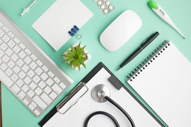 Vista aérea del escritorio del médico con píldoras y suministros de oficina.