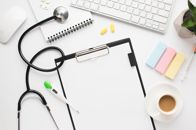 Vista aérea del escritorio médico con taza de café y notas adhesivas sobre la mesa