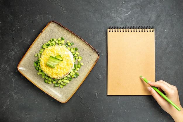 Vista aérea de la escritura a mano en el cuaderno y deliciosa ensalada servida con pepino picado sobre fondo oscuro