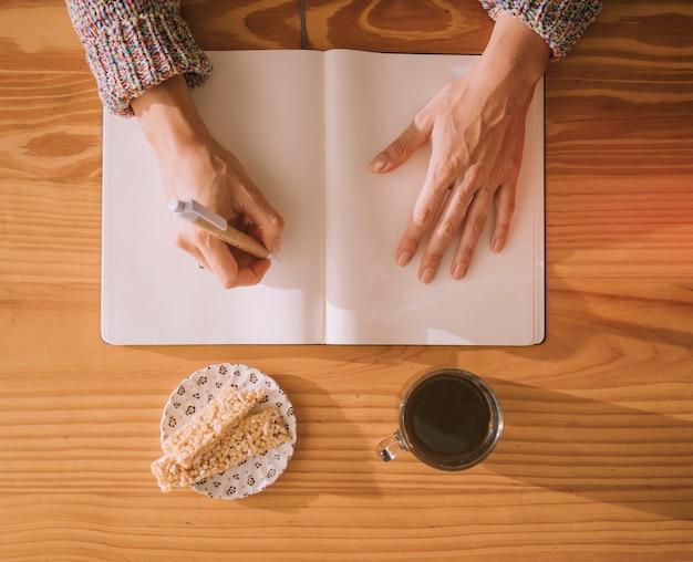 Una vista aérea de la escritura de la mujer en el cuaderno blanco en blanco con la pluma y el desayuno en la tabla