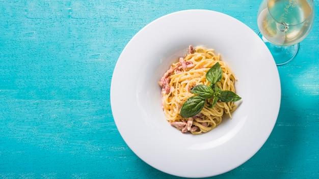 Una vista aérea de espaguetis con copa de vino sobre fondo turquesa