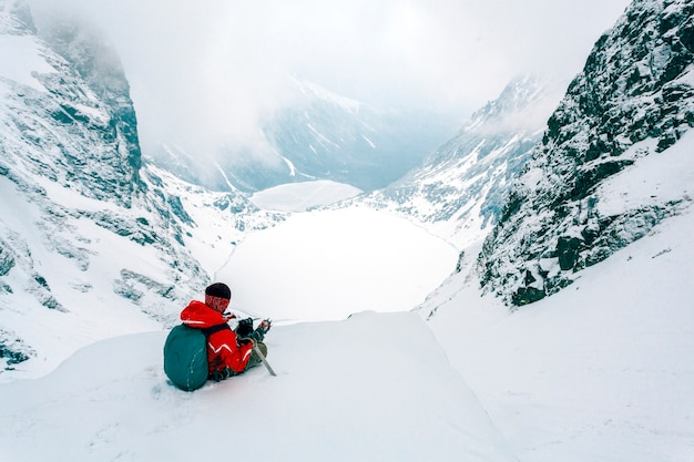 Una vista aérea del esquiador sentado en la cima de la montaña nevada de los alpes