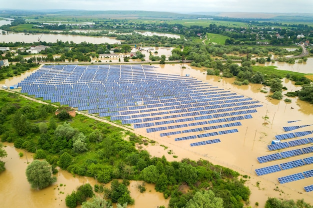 Vista aérea de la estación de energía solar inundada con agua de río sucia en temporada de lluvias