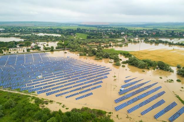 Vista aérea de la estación de energía solar inundada con agua de río sucia en temporada de lluvias.