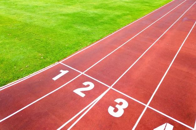 Vista aérea del estadio deportivo con pistas rojas con números y campo de fútbol de hierba verde.