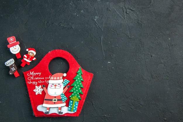 Vista aérea del estado de ánimo navideño con accesorios de decoración y caja de regalo de año nuevo en el lado derecho sobre una superficie oscura