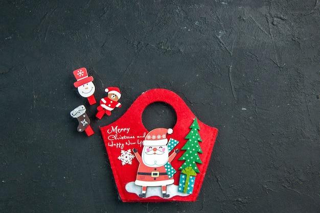 Vista aérea del estado de ánimo navideño con accesorios de decoración y caja de regalo de año nuevo en una superficie oscura