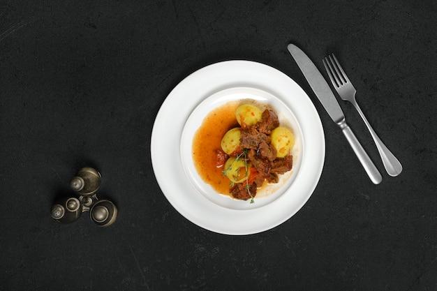 Vista aérea de estofado de cordero con patatas en un plato
