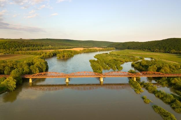 Vista aérea de un estrecho puente de carretera que se extiende sobre ancho río fangoso en zona rural verde.
