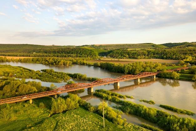 Vista aérea de un estrecho puente de carretera que se extiende sobre ancho río fangoso en zona rural verde
