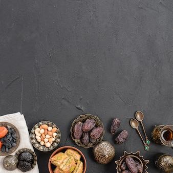 Una vista aérea de las fechas; placas metálicas de nueces y baklava sobre fondo negro con textura de hormigón con copia espacio