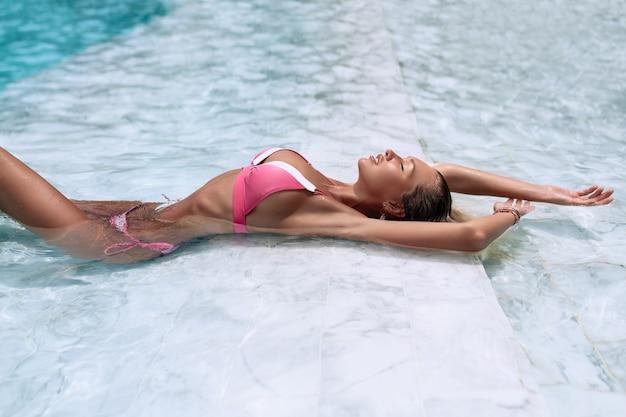Vista aérea figura sexual en una forma de bikini rosa deportiva junto a la piscina azul