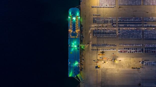 Vista aérea de filas de autos nuevos en la noche esperando ser despachados y enviados